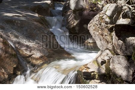 Close view of one of the small waterfalls at Franconia Notch, NH, on one of the many walking/hiking paths on a bright, sunny day.
