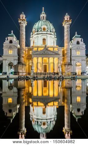Karlskirche or St. Charles's Church - one of famous churches in Vienna, Austria. Beautiful night photography with illumination and reflection in the water. Travel photo of Vienna.