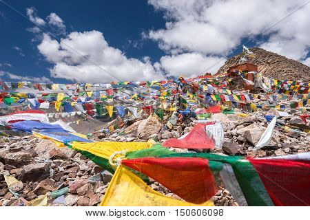 Three buddhist stupa with Buddhist prayer flags with blue sky at Khardung la pass,the highest (5,359 m, 17,582 ft) motorable pass on the world. Ladakh, Jammu and Kashmir, India.