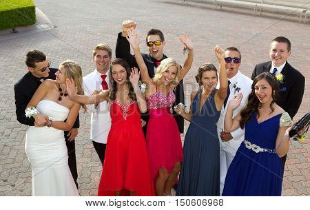 Large group of teenagers at the prom having fun outside laughing and smiling