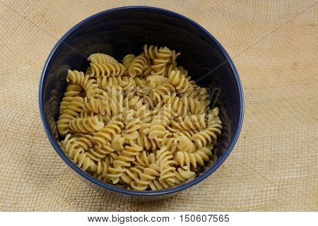 Cooked rotini whole wheat pasta in blue bowl