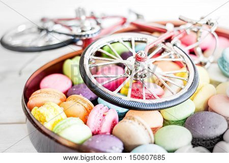 Macarons with bike model on wooden table.