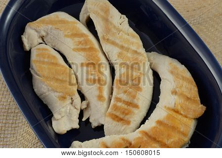 Close up of grilled turkey breast tenderloins in blue bowl on burlap for dinner preparatio