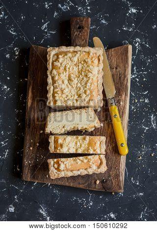 Ricotta orange tart on a rustic cutting board on dark background