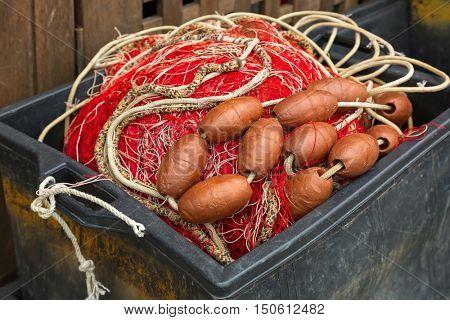 Plastic box full of red white fishing net, huge floats, nylon rope used in fishing industry