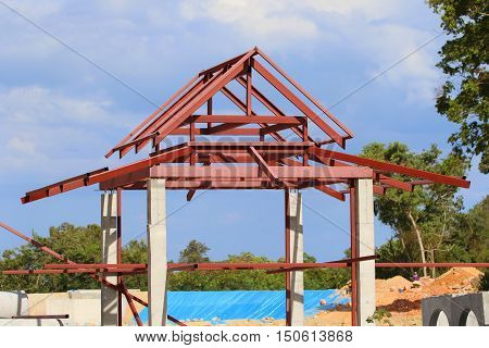 steel frame for a sun shelter, with concrete support pillars, distant workmen, near Songkhla