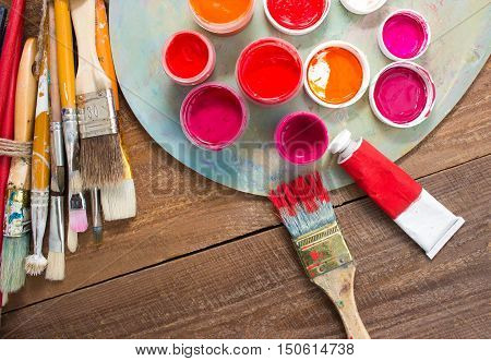 Paints, brushes and palette on the wood background. The workplace of the artist. Banner for school