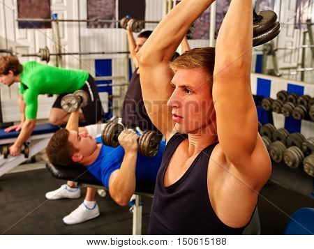 Group of handsome men working with dumbbells his body at Fitness Room with Free Weights