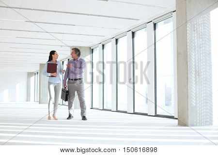 Businessman and businesswoman talking while walking in empty office