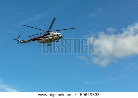 Kamchatka Peninsula, Russia - August 13, 2016: Tourist helicopter against the blue sky. South Kamchatka Nature Park. View from the helicopter.
