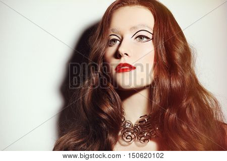 Vintage style portrait of young beautiful woman with long curly hair, fancy make-up and stylish glass necklace