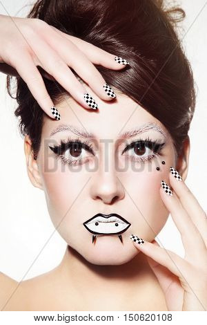 Vintage style close-up portrait of young beautiful girl with fancy gothic make-up and checked manicure