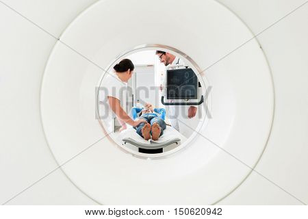 Doctor, nurse, and patient at CT scan tomography in hospital, shot through the tube of device