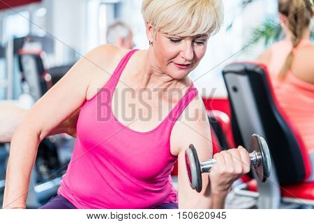 senior woman working out with dumbbells at the gym