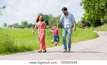 Family letting kid fly in summer walk holding daughter by the hands