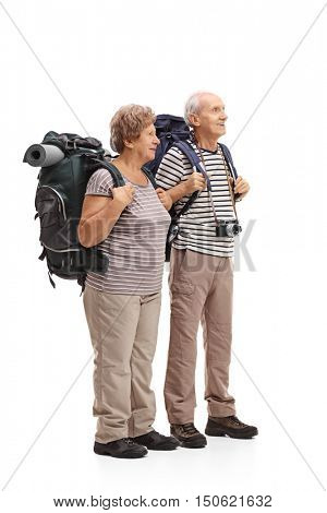 Full length profile shot of two elderly hikers looking in the distance isolated on white background