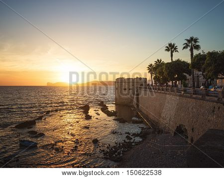 Sun Sets over Capo Caccia Cliffs Viewed from the City of Alghero Sardinia Italy