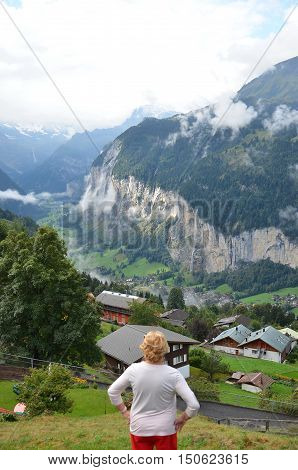 Woman looking at mountains and valley view. Tourist  woman looking forward on mountain landscape background. Senior woman standing admiring a mountaintop view. Travel concept. Switzerland. Wengen