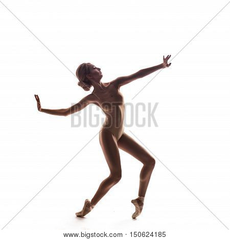 Ballerina in beige outfit posing on toes. Isolated on white background