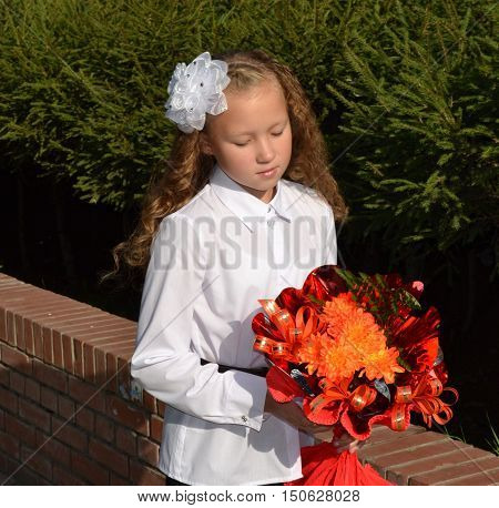 Girl with a white bow with a bouquet of standing with downcast eyes