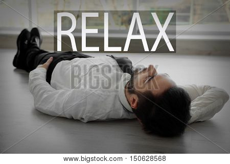 Word RELAX and young businessman lying on the floor.