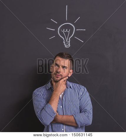 Handsome young pensive man is looking away rubbing his chin and thinking standing against blackboard with drawn electric lamp