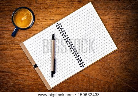 Open notebook with pen and coffee cup on wooden background. Top view