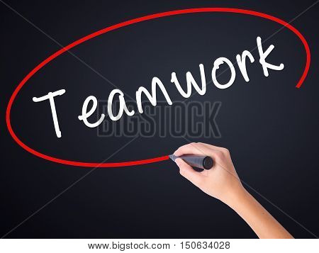 Woman Hand Writing Teamwork With A Marker Over Transparent Board
