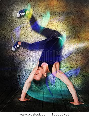 The break dancer doing handstand against colorful wall background