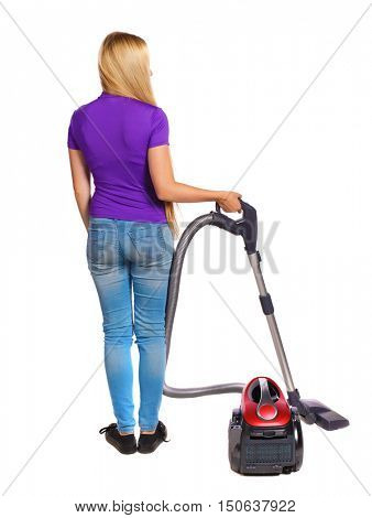Rear view of a woman with a vacuum cleaner. She is busy cleaning. Rear view people collection.  backside view of person.  Isolated over white background. Long-haired blonde in the purple shirt holding