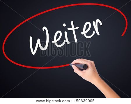 Woman Hand Writing Weiter (continue In German)  With A Marker Over Transparent Board