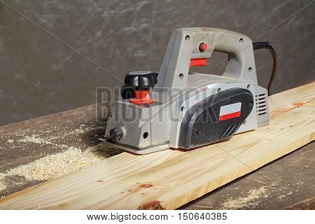 the electric planer is lying on a wooden table