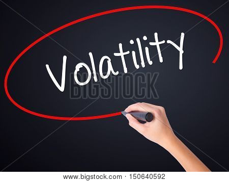 Woman Hand Writing Volatility With A Marker Over Transparent Board