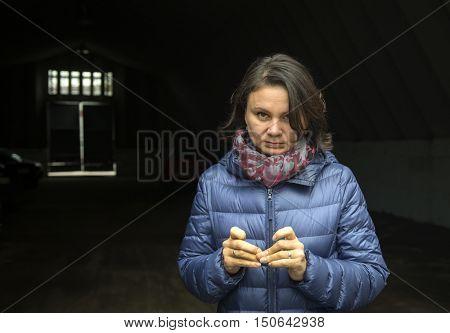 Tired sad woman. Street Photography. Black background.