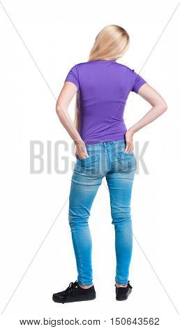 back view of standing young beautiful  woman.  girl  watching. Rear view people collection.  backside view of person.  Long-haired blonde in the purple shirt stands with his hands back pockets of his