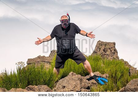 Obese diver confused he is at top of the mountain instead shore of the sea.
