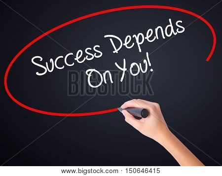 Woman Hand Writing Success Depends On You! With A Marker Over Transparent Board