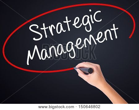 Woman Hand Writing Strategic Management With A Marker Over Transparent Board .