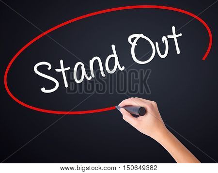 Woman Hand Writing Stand Out With A Marker Over Transparent Board