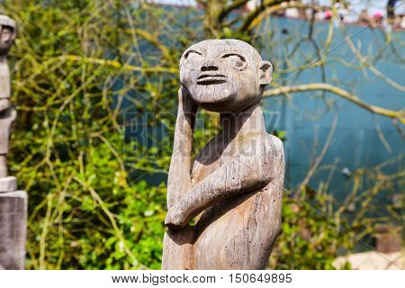 Asian old wooden statue of idol in the park