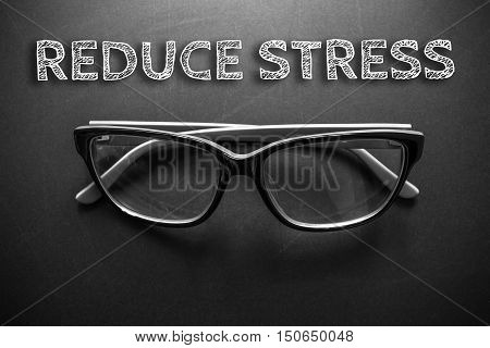 Text reduce stress with eyeglasses on black background / business concept / dark tone