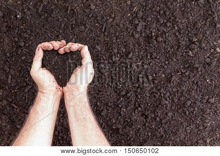 Pair Of Hands Holding Soil In Heart Shape
