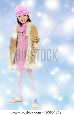 Happy little girl in a pink hat and winter coat with fur. Girl posing in full growth.Blue Christmas festive background with white snowflakes.