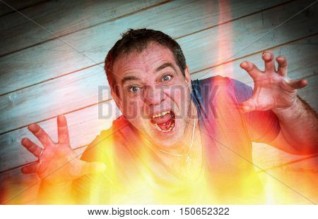 Portrait of aggressive man through the flames. Artistic artifact and dust