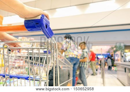 Closeup of female shopper with trolley at supermarket waiting at check-out - Young woman waiting to pay at shopping center - Consumerism concept - Warm filter