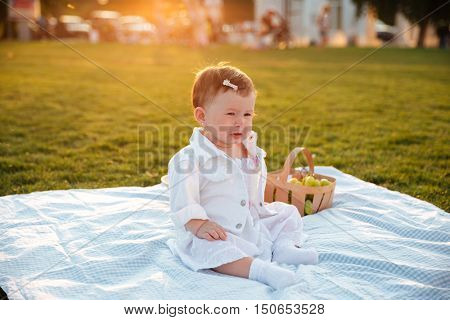 Little baby sitting and crying alone on picnic in park