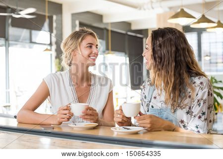 Two beautiful young women holding cup of coffee and talking to each other. Young blonde woman in conversation with her best friend while sipping a cup of capuccino. Friends meeting up for coffee.
