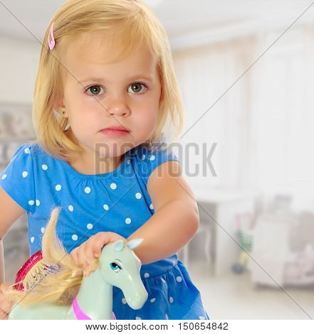 Cute little blonde girl playing with a toy horse. Girl wearing a blue dress with polka dots.On the background of the school hall with large Windows.