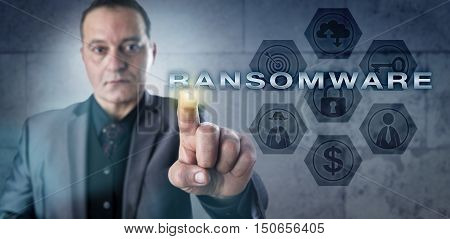 Mature cyber investigator is touching RANSOMWARE onscreen. information technology concept and cyber security metaphor malicious software that restricts data access to extortionate ransom money.
