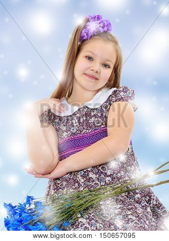 Happy little girl with a big purple bow on her head , and fancy dress. In the lap of the girls lay a bouquet of blue flowers.Blue Christmas background with white snowflakes.